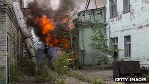 A fire burns in a factory complex hit by a rocket during fighting between pro-Russia rebels and Ukrainian government troops in Donetsk