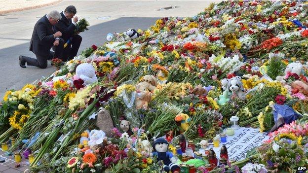 Ukrainian President Petro Poroshenko (R) and Dutch ambassador to Ukraine Kees Klompenhouwer kneel down and cross themselves during a flower-laying ceremony in Kiev (21 July 2014)
