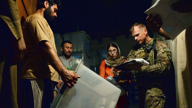 A NATO soldier in Jalalabad takes note of a ballot box for delivery to Kabul for a complete audit of all votes