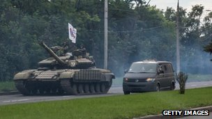 Pro-Russia rebels travel in a convoy of tanks and transport vehicles as fighting escalates in Donetsk