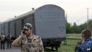 A pro-Russian rebel speaks on the phone as a refrigerated train loaded with bodies of the passengers departs the station in Torez