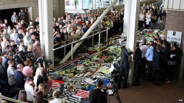 A group of people gathered round football shirts and flowers laid on the ground outside St James' Park football stadium