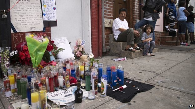 Pedestrians sit near a memorial for Eric Garner erected near the site of his death in New York on 19 July 2014