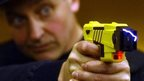Police officer firing taser