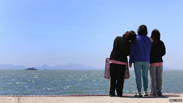 Relatives of passengers who died when the Sewol ferry sank look out to the sea at the port in Jindo - 30 April 2014