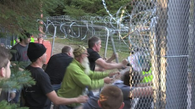 protesters pushing the fence