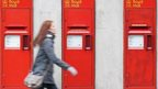 A woman walking past a Royal Mail post office