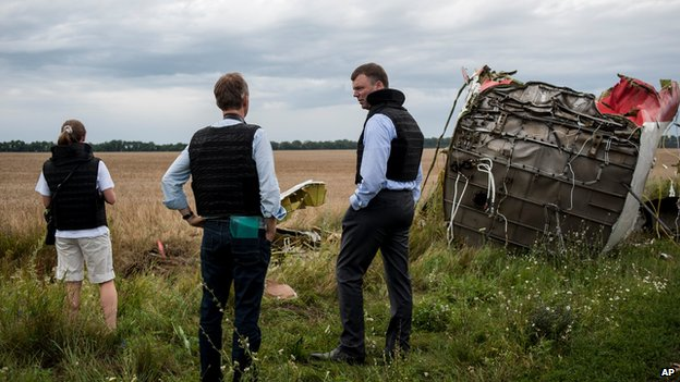 Alexander Hug, centre, deputy head of the OSCE mission, stands at the crash site
