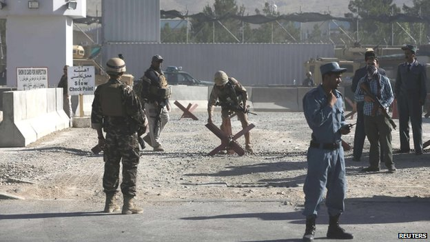 Afghan and foreign security personnel stand guard at the site of a blast (22 July 2014)