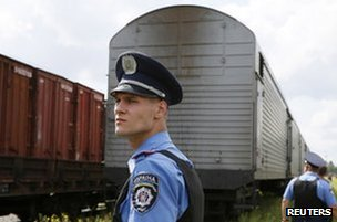 A Ukrainian policeman watches as the train carrying bodies arrives in Kharkiv, 22 July