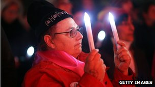 A member of the public holds candles to mourn the victims of HIV/Aids and those who died on flight MH17 during a candlelight vigil at Federation Square, Melbourne