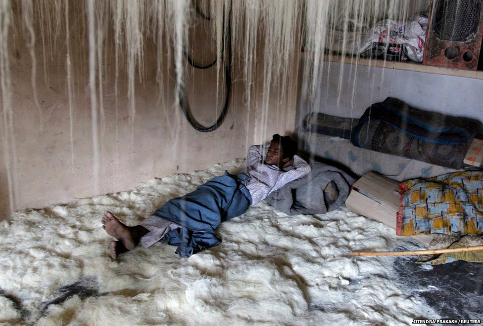 A worker rests on vermicelli inside a factory in the northern Indian city of Allahabad