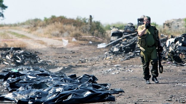 Armed man near body bags at the site of the crashed MH17 plane in Ukraine, 21 July 2014