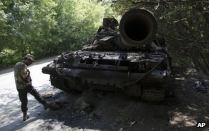 A rebel checks burnt tank near Donetsk, 22 July