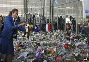 A KLM employee holds a toy near a sea of tributes to the dead at Schiphol airport, Amsterdam, 22 July
