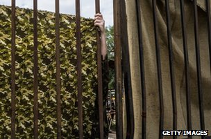 A camouflage sheet is hung for privacy at the tank factory in Kharkiv where the bodies have been brought, 22 July