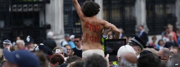 A woman protesting outside Westminster with 'Stop FGM' written on her back