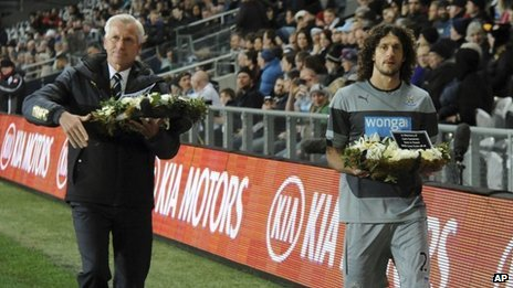 Alan Pardew and captain Fabricio Coloccini carrying wreaths in memory of the two victims