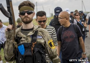 A rebel guards Malaysian air crash investigators near the village of Grabove, east Ukraine, 22 July