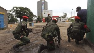 Congolese security officers position themselves as they secure the street near the state television headquarters (C) in the capital Kinshasa, 30 December 2013