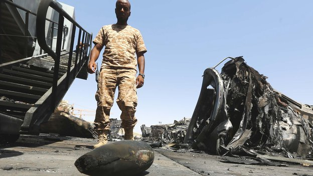 A militiamen at Tripoli airport in Libya amidst the debris of shelled planes - July 2014