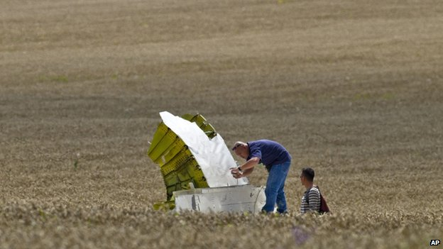 A man taking a picture of a piece of aircraft wreckage in a field