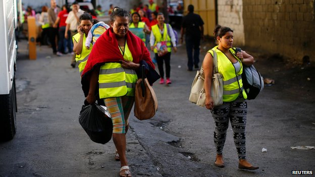 Residents of the Tower of David leave the building in Caracas, 22 July 2014
