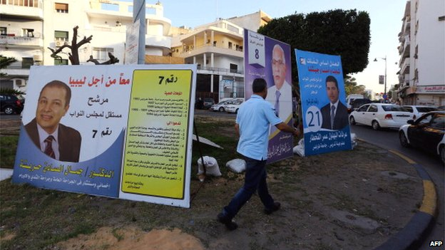 A Libyan man walks past parliamentary campaign posters in the capital Tripoli on 22 June 2014