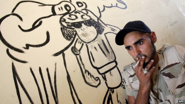 A Libyan fighter smokes a cigarette next to graffiti depicting slain Libyan leader Muammar Gaddafi in the coastal city of Benghazi in October 2012