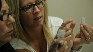 Women hold vials
