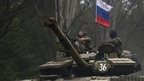 A pro-Russian rebel looks up while ridding on a tank flying Russia's flag, on a road east of Donetsk