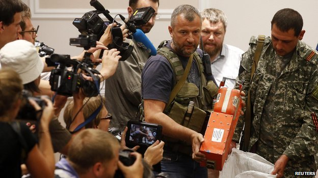 A pro-Russian separatist shows members of the media a black box