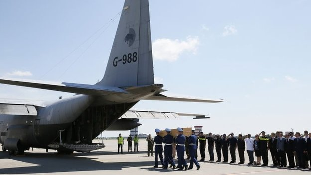 Honour guards carry a coffin of one of the victims of Malaysia Airlines MH17 at Kharkiv airport (23 July 2014)