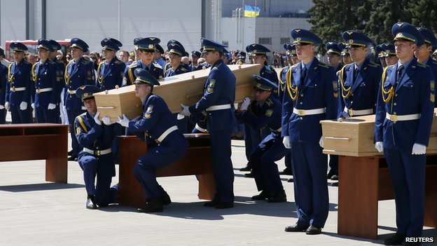 Honour guards carry a coffin of one of the plane crash victims