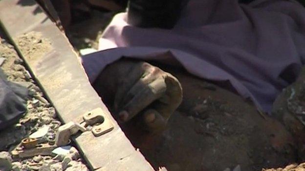 Hand of Asmaa el-Helou underneath a pile of rubble in Sheja'iya