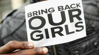 A man holds a sign which reads Bring Back Our Girls
