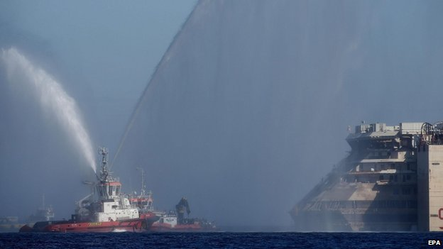 A tugboat accompanies the Costa Concordia as it begins its final journey to the port of Genoa (23 July 2014)
