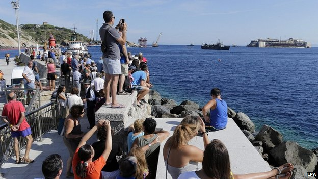 Locals and tourists watch the wrecked Italian cruise liner the Costa Concordia begin its final journey to the port of Genoa (23 July 2014)