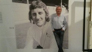 Andy Potter next to a large photo of Roy McFarland