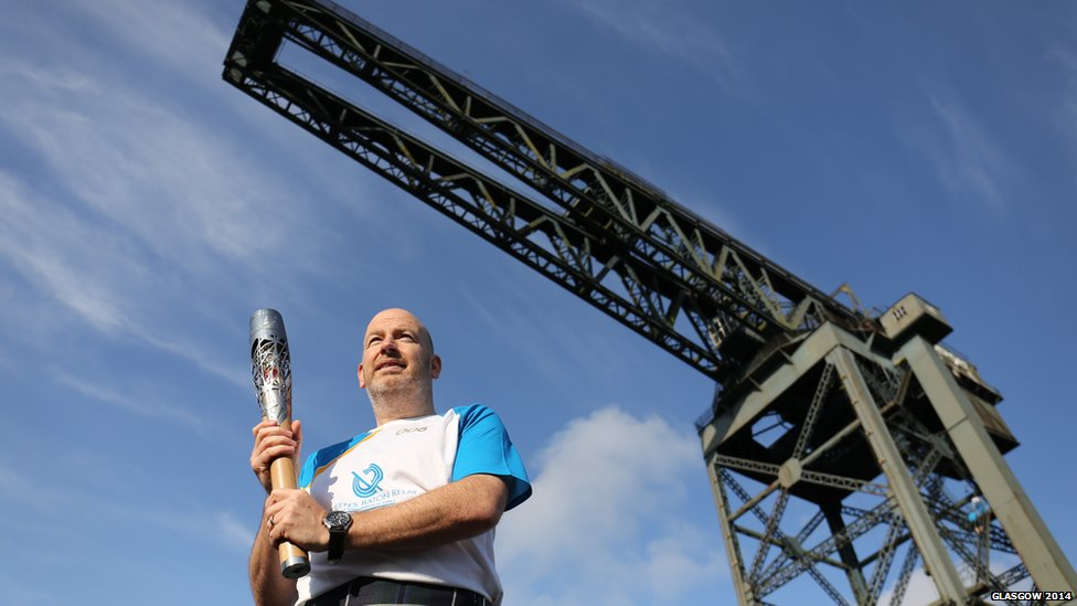 Mark O'Sullivan carries the Glasgow 2014 Queen's Baton at Finnieston Crane in Glasgow