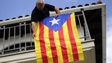 A man hangs a Catalan flag at his balcony near Barcelona in 2013