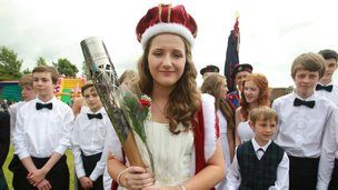The Queen of a Summer Festival poses with the Queen's Baton