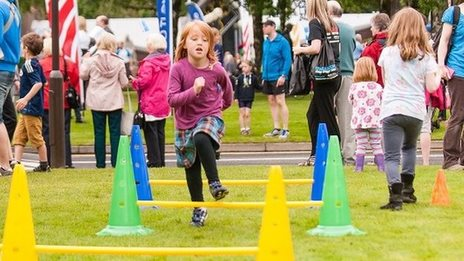 young girl runs on a simple hurdling course