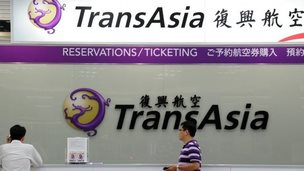 Local journalists wait in front of a TransAsia reservations desk at the Sungshan airport in Taipei, 23 July  2014