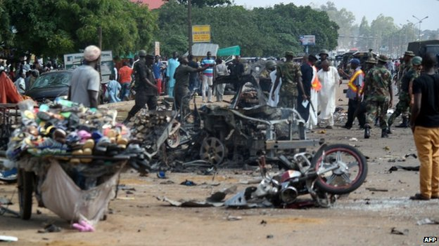 People stand near a wrecked car after a bomb exploded on July 23, 2014 in Kaduna, north of Nigeria