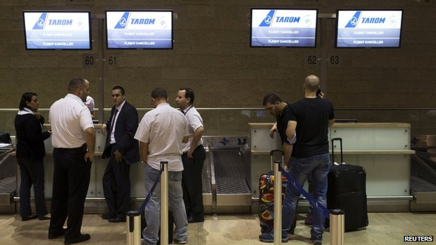 Passengers and airline staff stand near a check-in desk of an airline that cancelled its flight out of Tel Aviv at Ben Gurion International airport on 22 July 2014