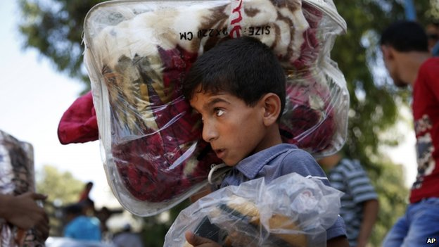 A Palestinian youth carries blankets donated to the UN school where hundreds of families sought refuge on 23 July Wednesday, July 23, 2014.