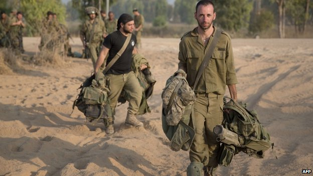Israeli soldiers return from the Gaza Strip at an army deployment area near Israel's border with the besieged Palestinian territory on 23 July 2014
