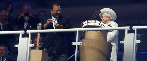 Prince Imran laughs after struggling to open the baton as The queen looks on