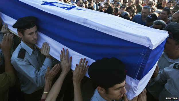 "A mourner touches the flag-draped coffin of Israeli soldier Natan Cohen, killed during fighting in Gaza on Tuesday, during his funeral in Modi""in, a town between Jerusalem and Tel Aviv, July 23, 2014."